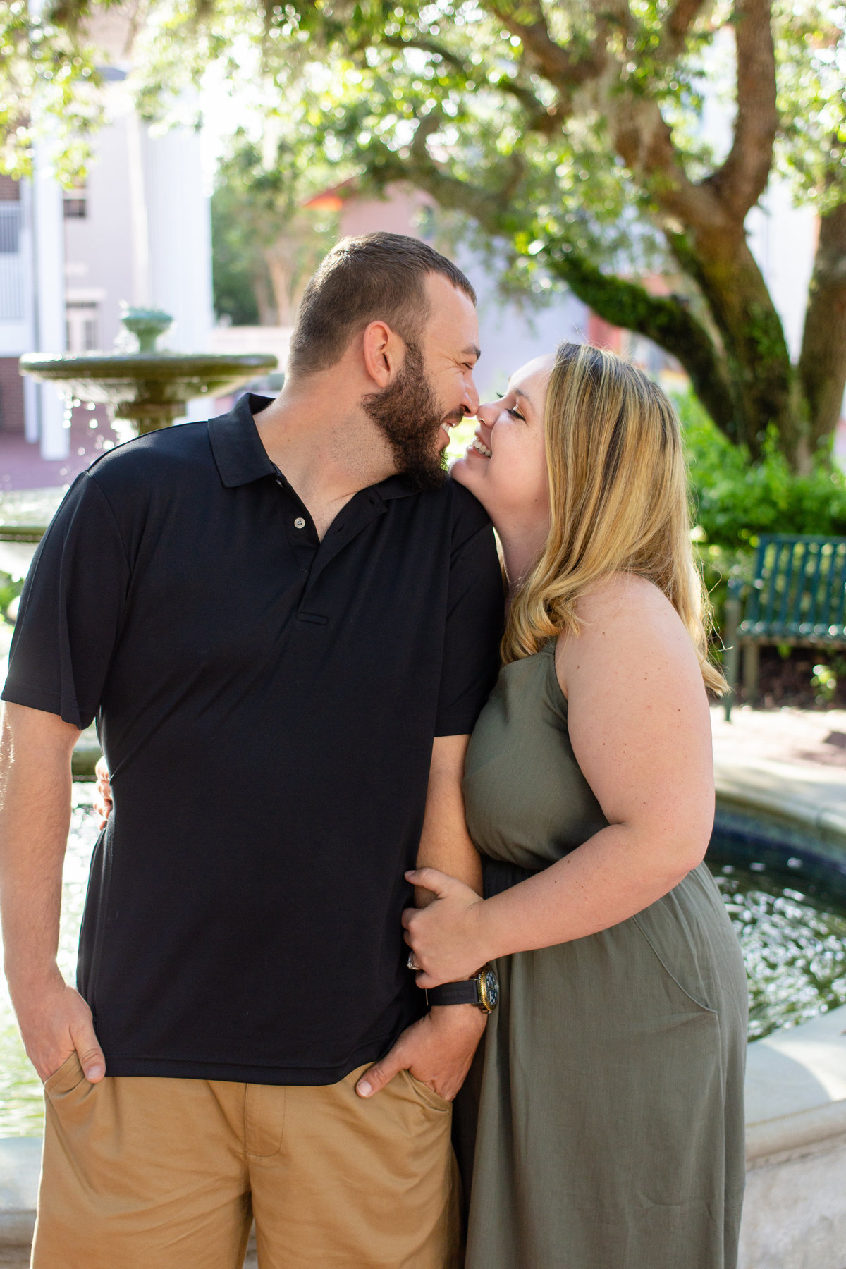 Couple smiles sweetly at each other in Celebration, Florida during their engagement photos