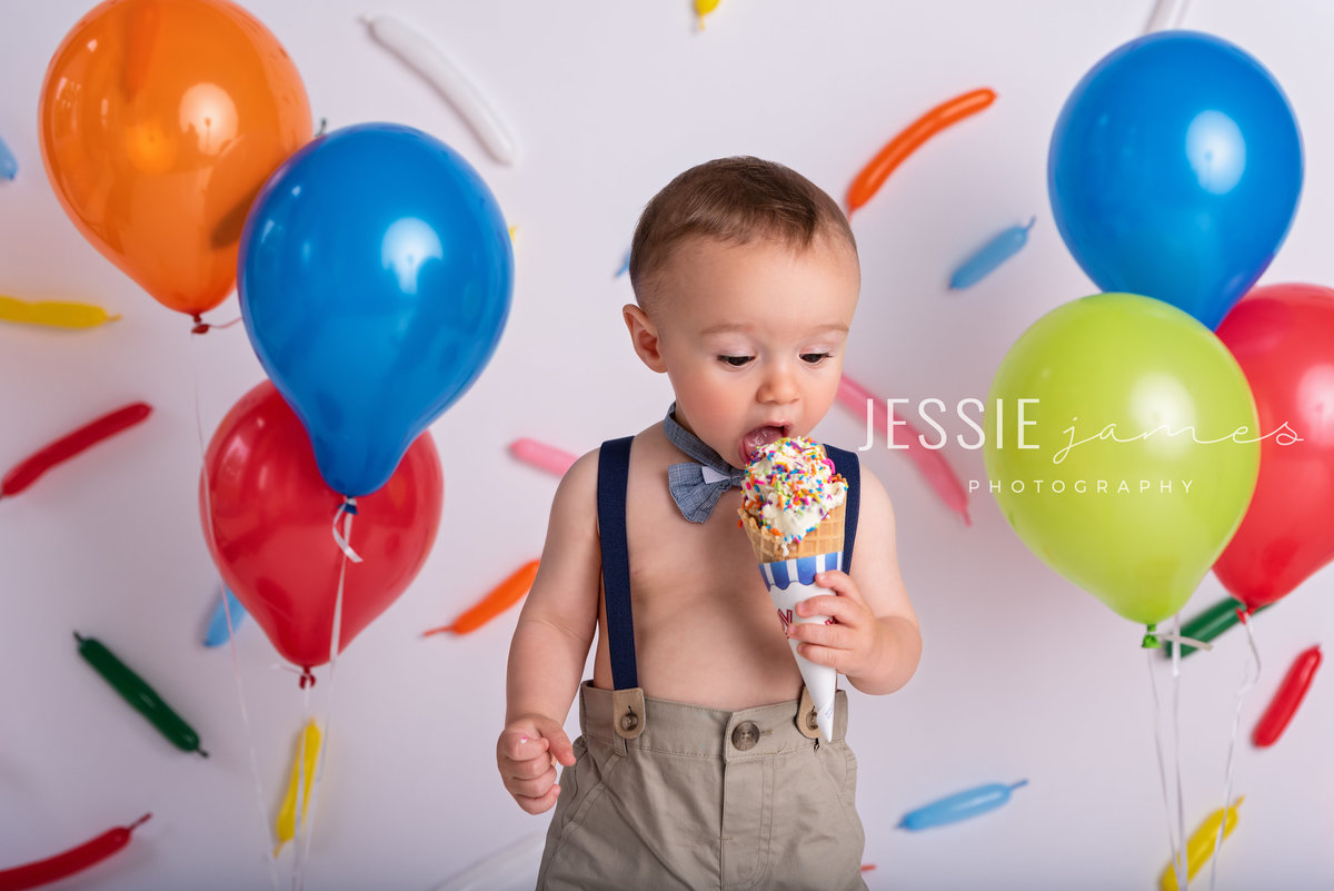 baby boy eating an ice cream cone in front of a backdrop with sprinkles made out of balloons