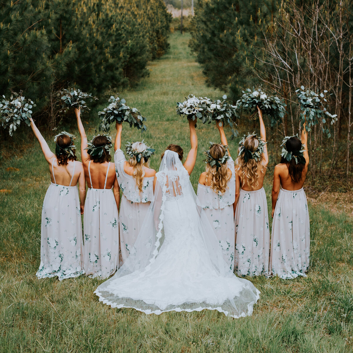 Boho bridesmaids and bride stand in a field with their bouquets in the air, wearing floral crowns at a rustic wedding.