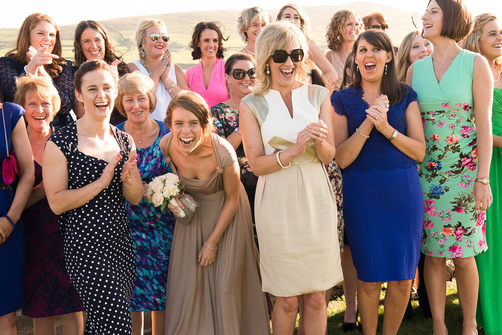 Many female wedding guests in colourful outfits laughing together with bridesmaid with taupe bridesmaid dress