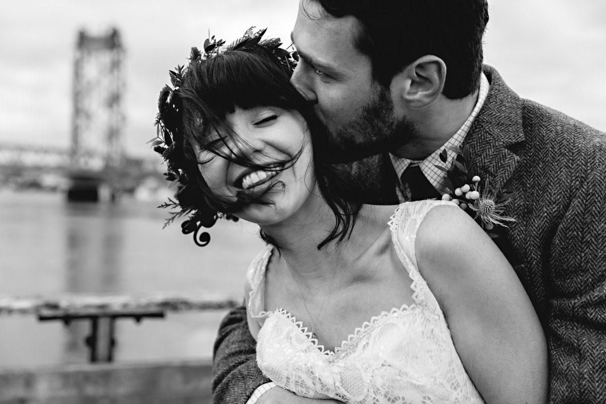 The bride laughs as the groom grabs her tight for a kiss on their wintery Portsmouth NH elopement