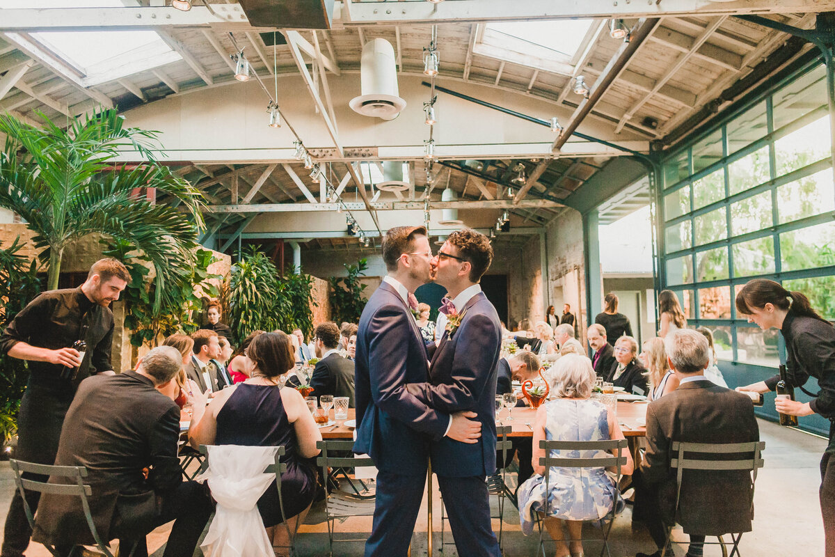 Gay couple kisses at their wedding reception