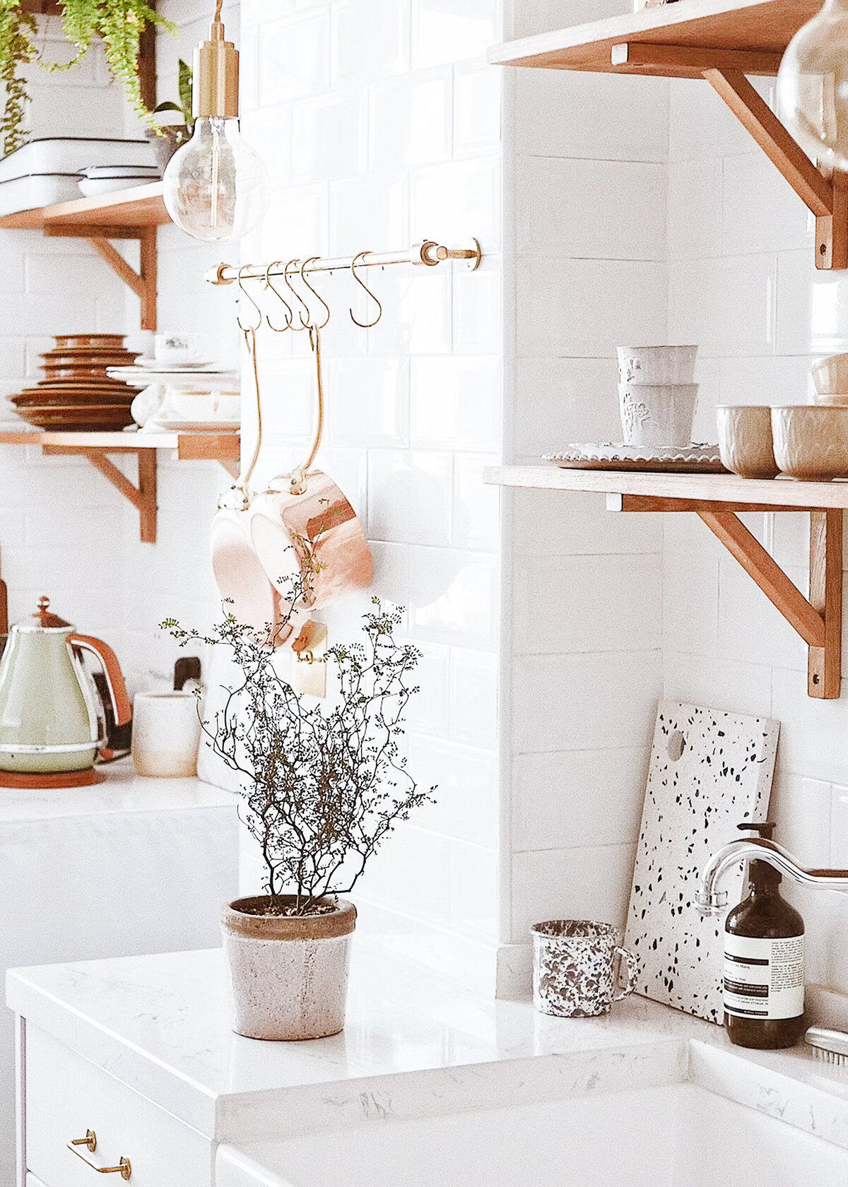 A white kitchen is styled with copper pans and a terrazzo chopping board. Kitchen interior decor inspiration.