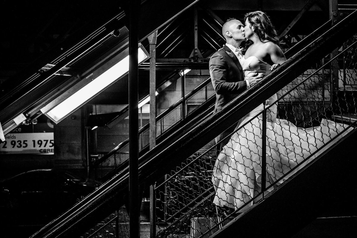 A couple kisses on the El tracks after their Carnivale wedding.