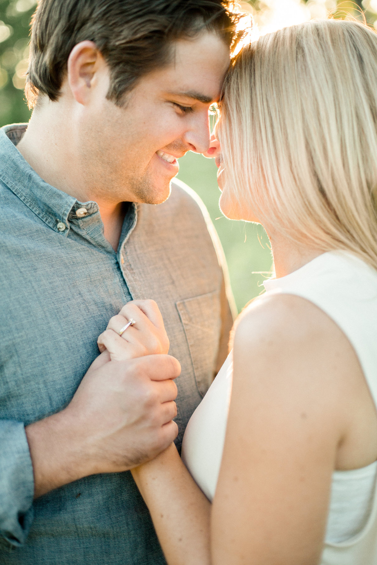forehead to forehead pose holding hands in summer light engagement photography minnesota