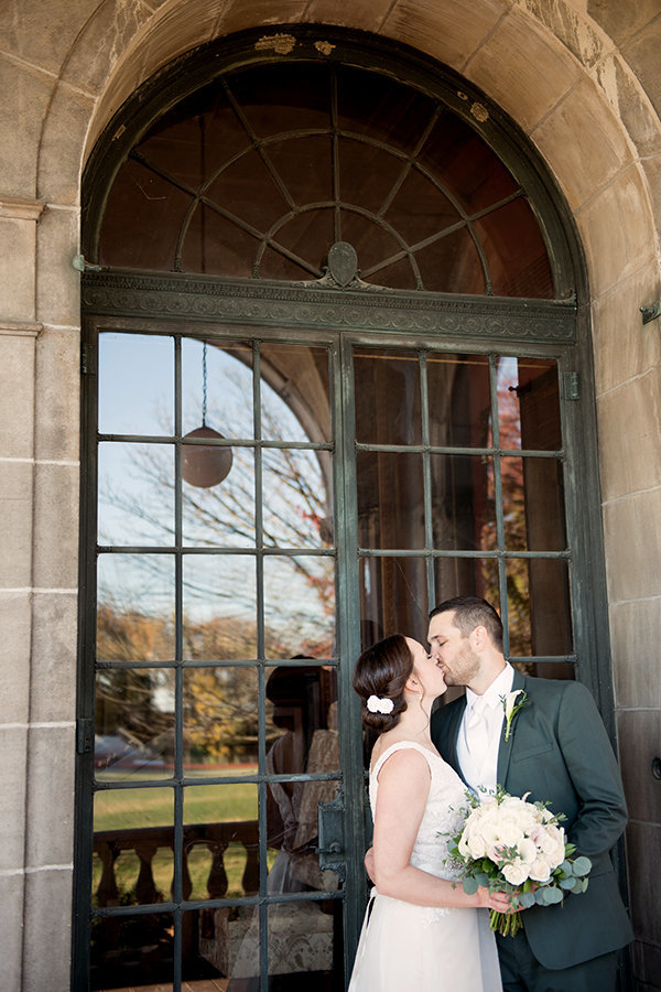 A bride and groom kiss by the window of The Patio at Archmere Academy