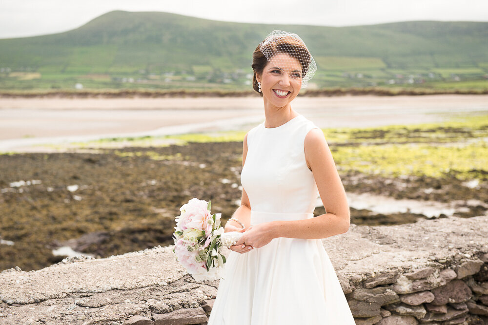 brunette bride wearing a birdcage veil and tea-length, vintage wedding dress, holding a bouquet with light pink roses while standing by a stone wall with the sea and mountains in the background