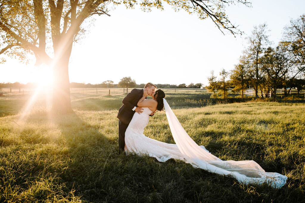 a beautiful bride and groom kissing with the sunset in the background, sunlight shining through the trees, the bride has a long gown with a trailing veil