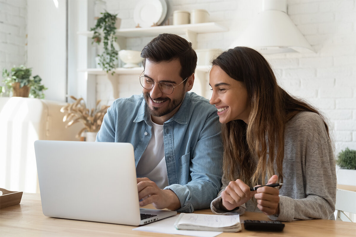 happy young couple working together on computer with calculator