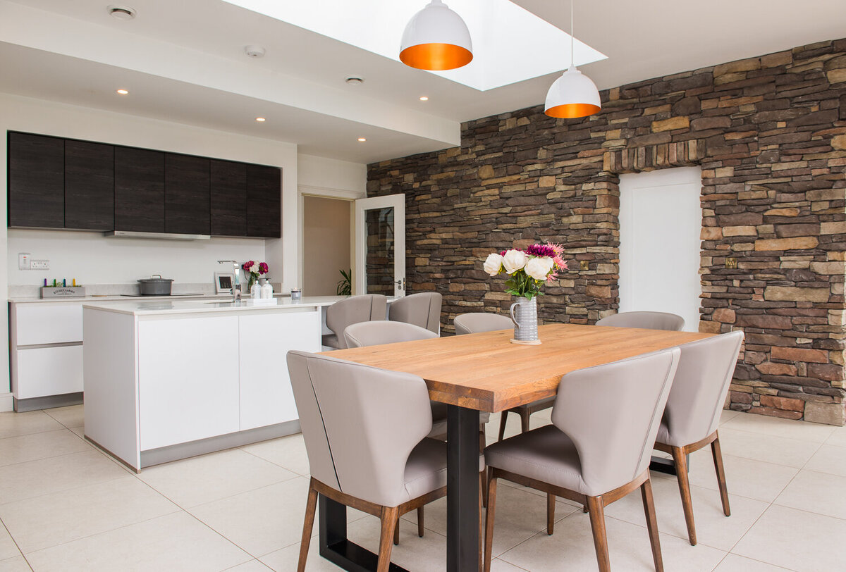 Modern kitchen with white gloss units and exposed stone walls