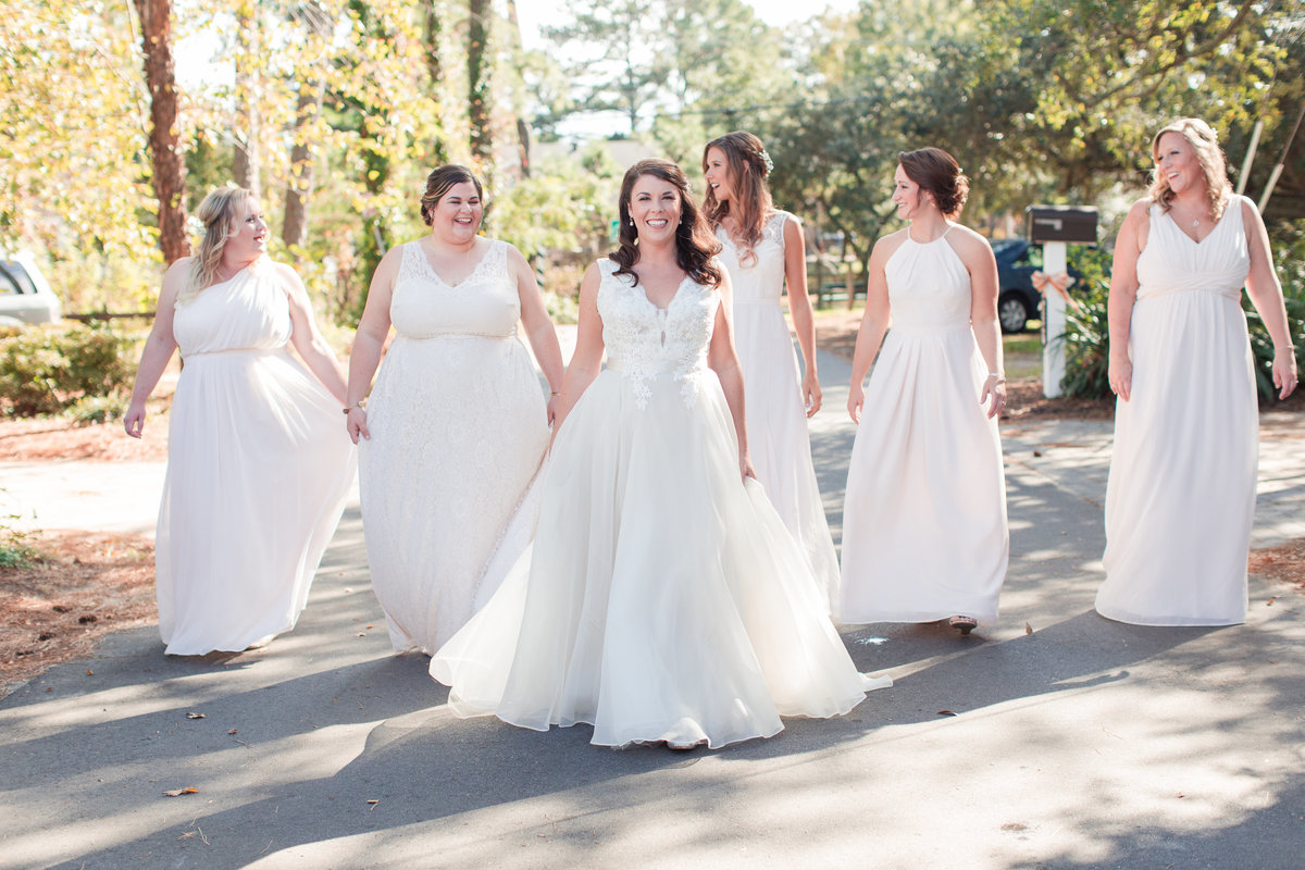 bride and bridesmaids walking down the street and smiling on a sunny day