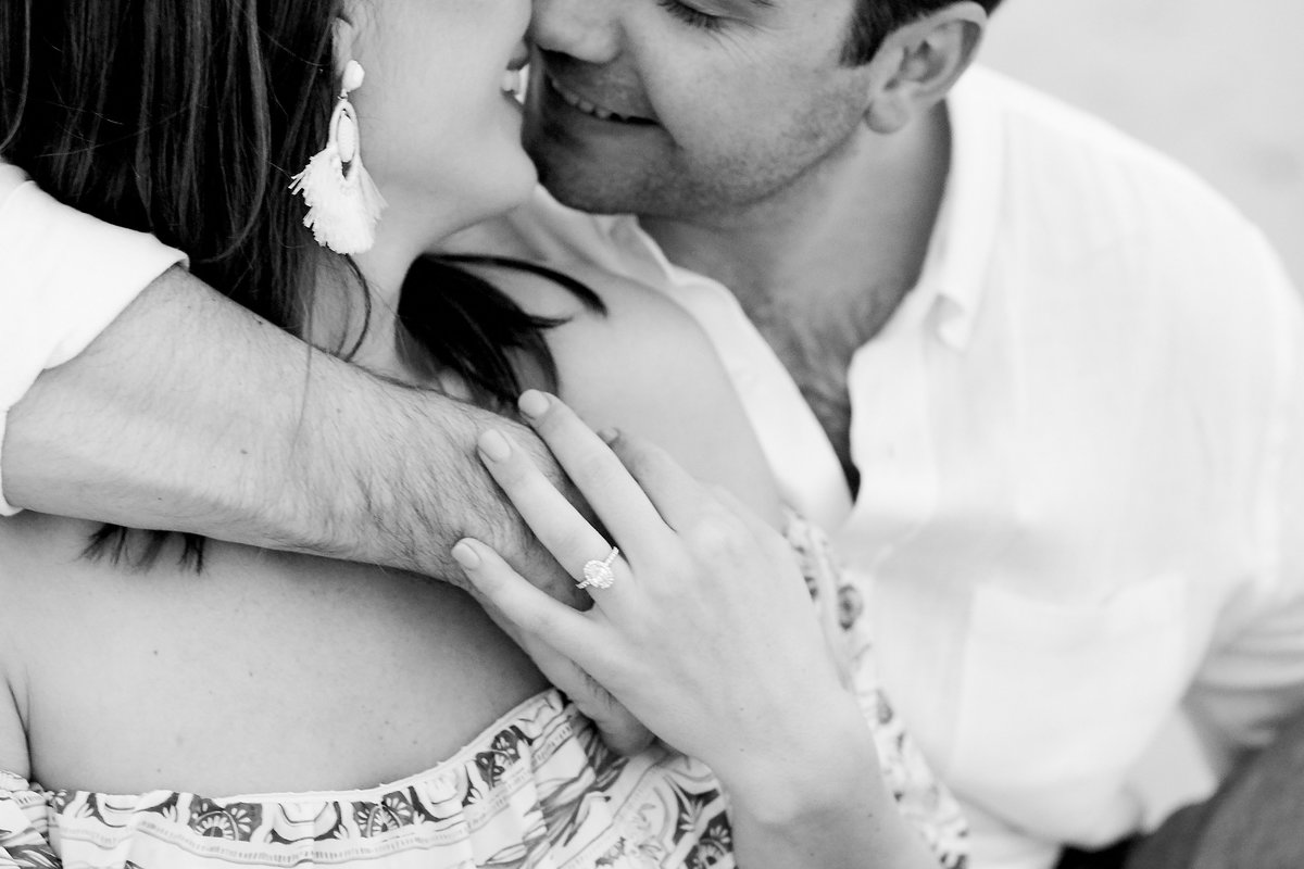 black and white of boy and girl kissing in a downtown charleston beach engagement session