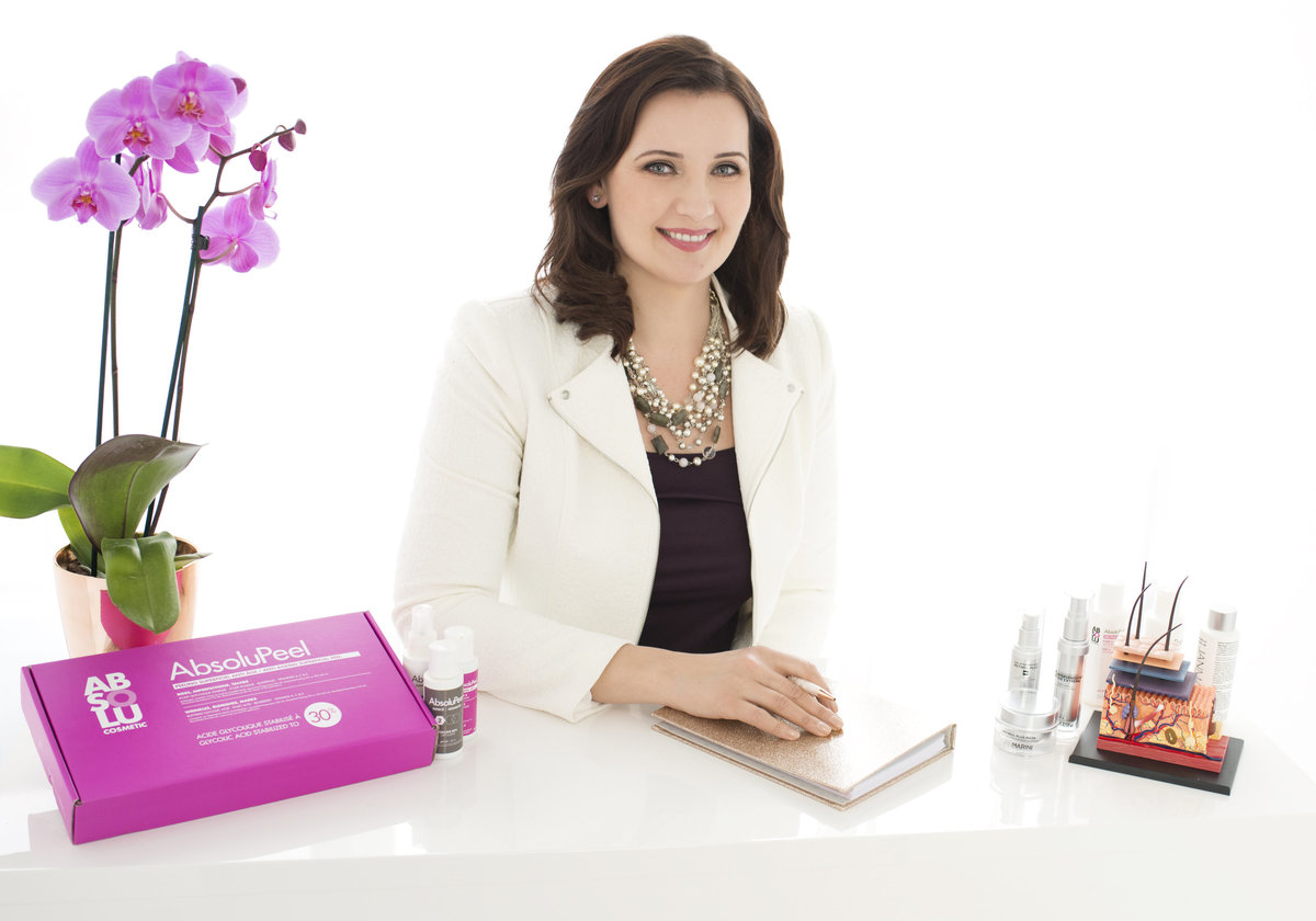 exceutive head shot of  business owner  sitting on her  office desk  with  flowers wearing white  jacket looking in the camera and  smiling  professional