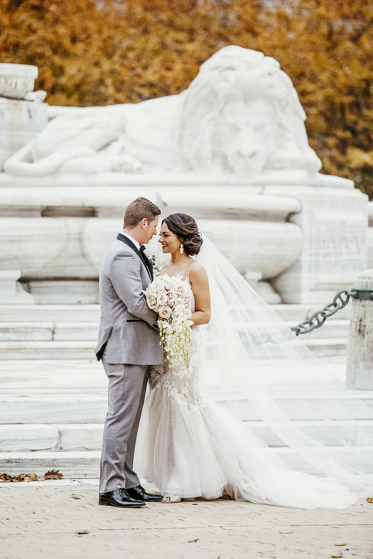Autumn wedding with bride and groom embracing in front of monument in Buffalo, New York