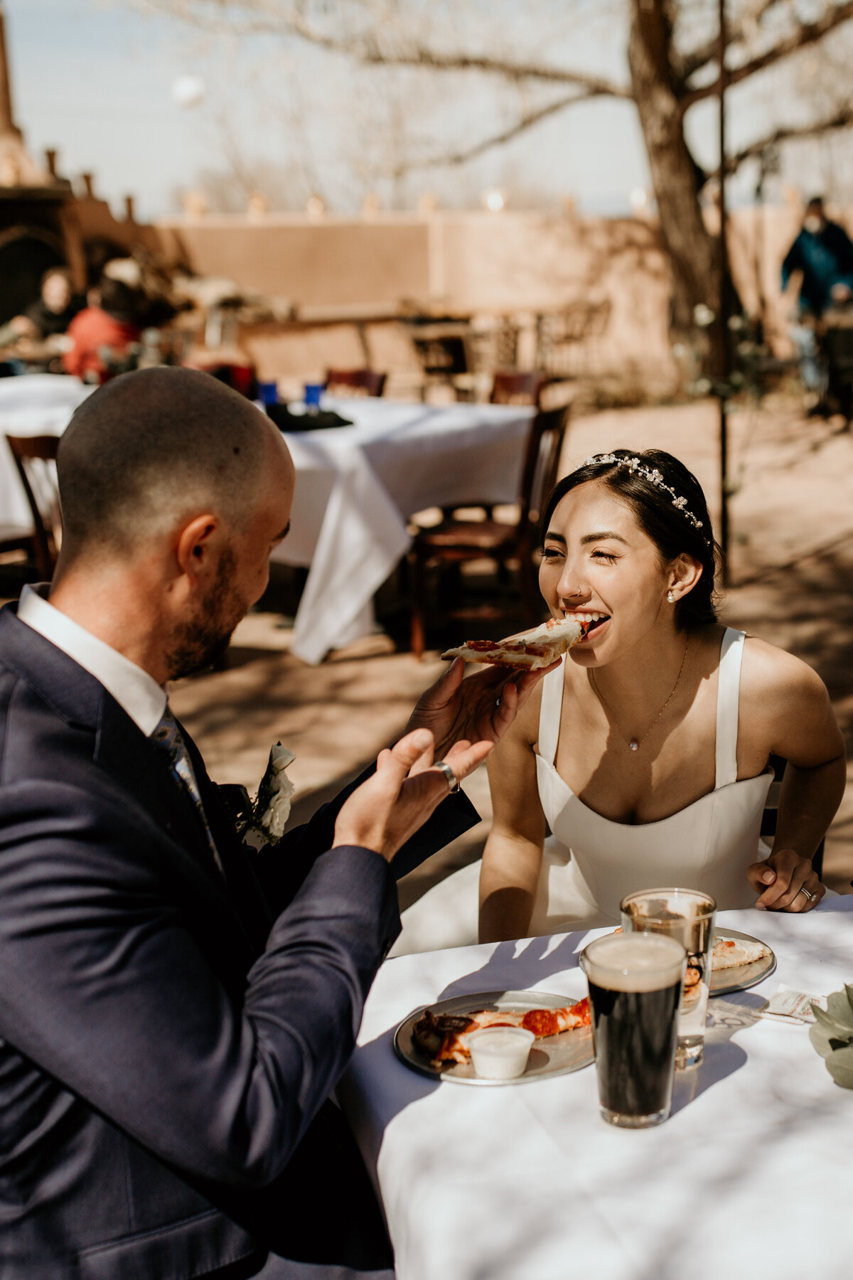 groom feeding bride pizza at a brewery