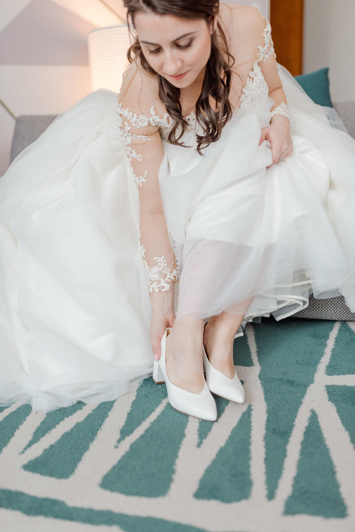 bride putting on white heals on a green carpet