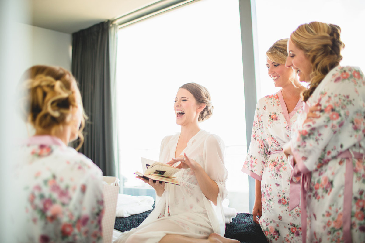 bride and bridesmaids opening a present at the midland hotel and laughing