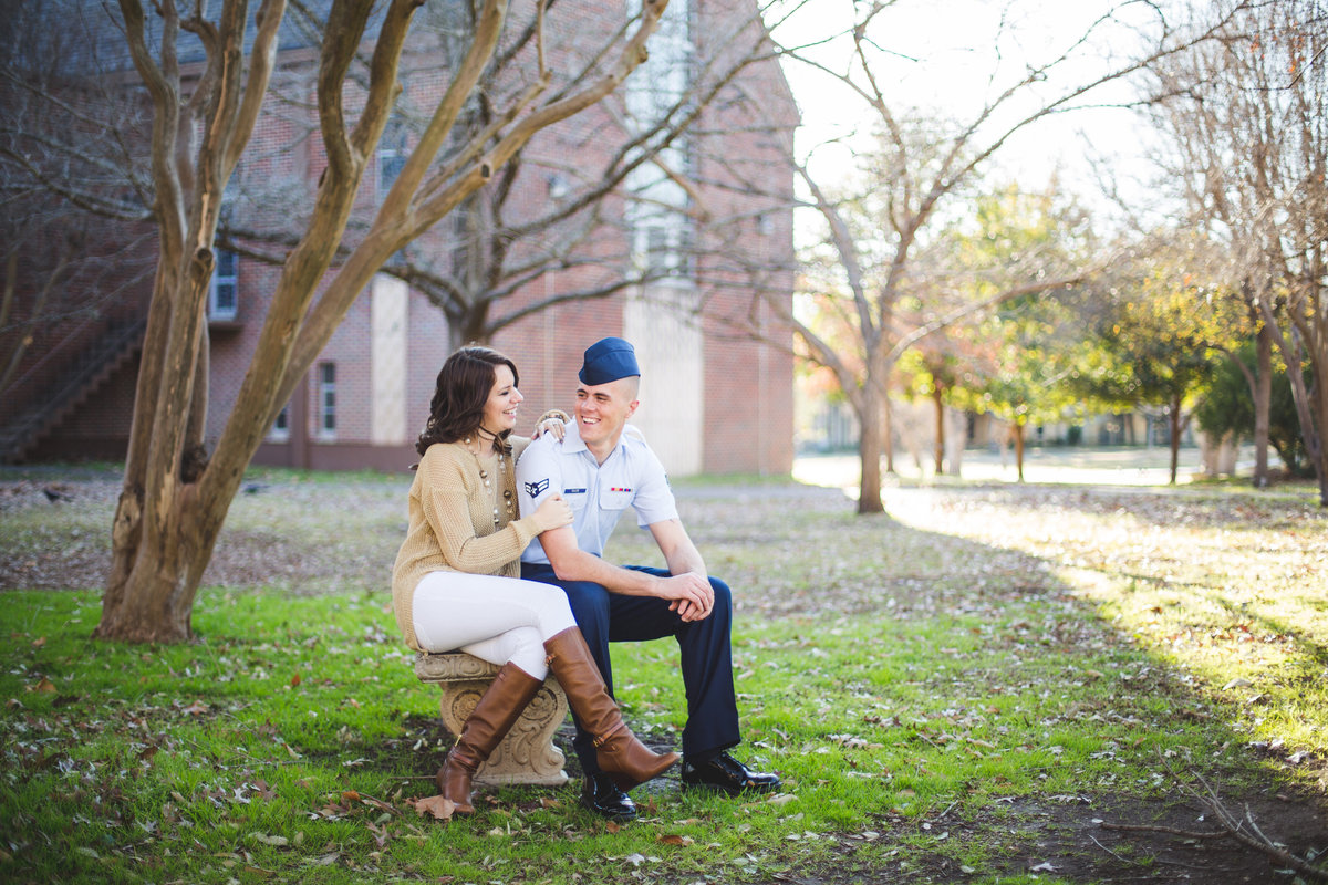 Engaged Airman and his fiancé sitting on a bench looking into each others eyes at their engagement photography session.