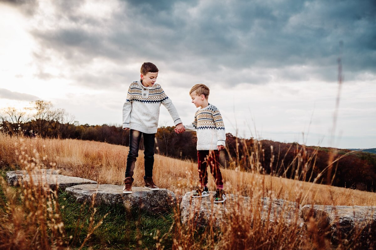 Two brothers in patterned sweaters, holding hands and standing on rocks with stormy skies behind them and golden wheat around them.