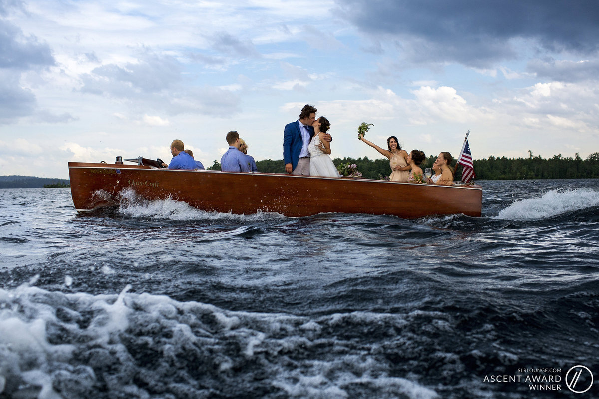 The bride and groom kiss on board a boat under a stormy sky with their wedding party on Squam Lake New Hampshire after a Church Island ceremony