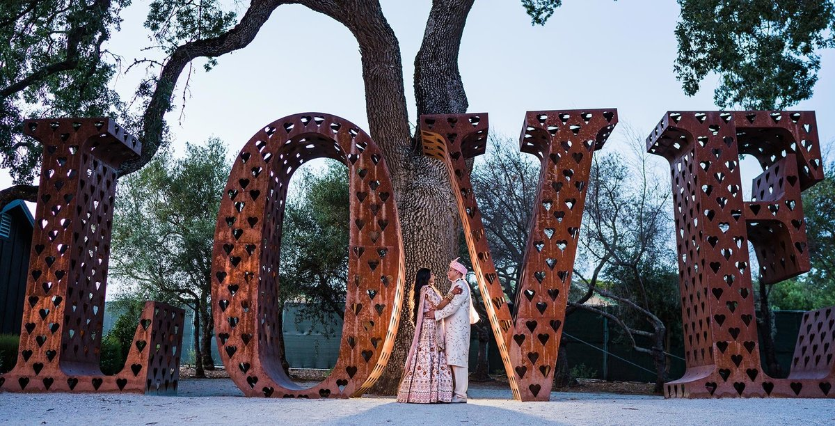 Couple in front of Love sign