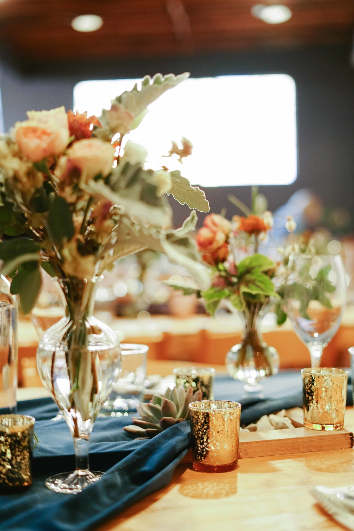 Dinner party table setting with blue table runner and pink floral arrangements