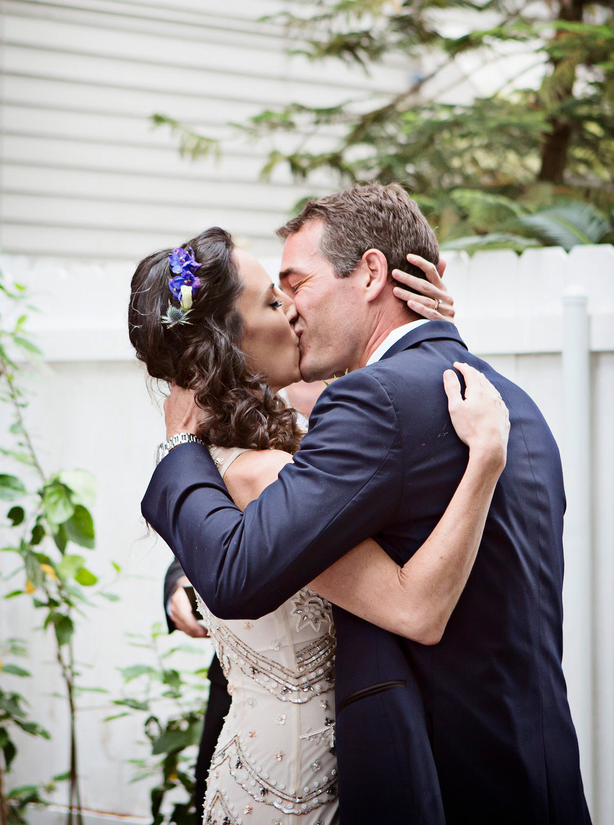 bride and groom kiss during wedding ceremony in The Garden District