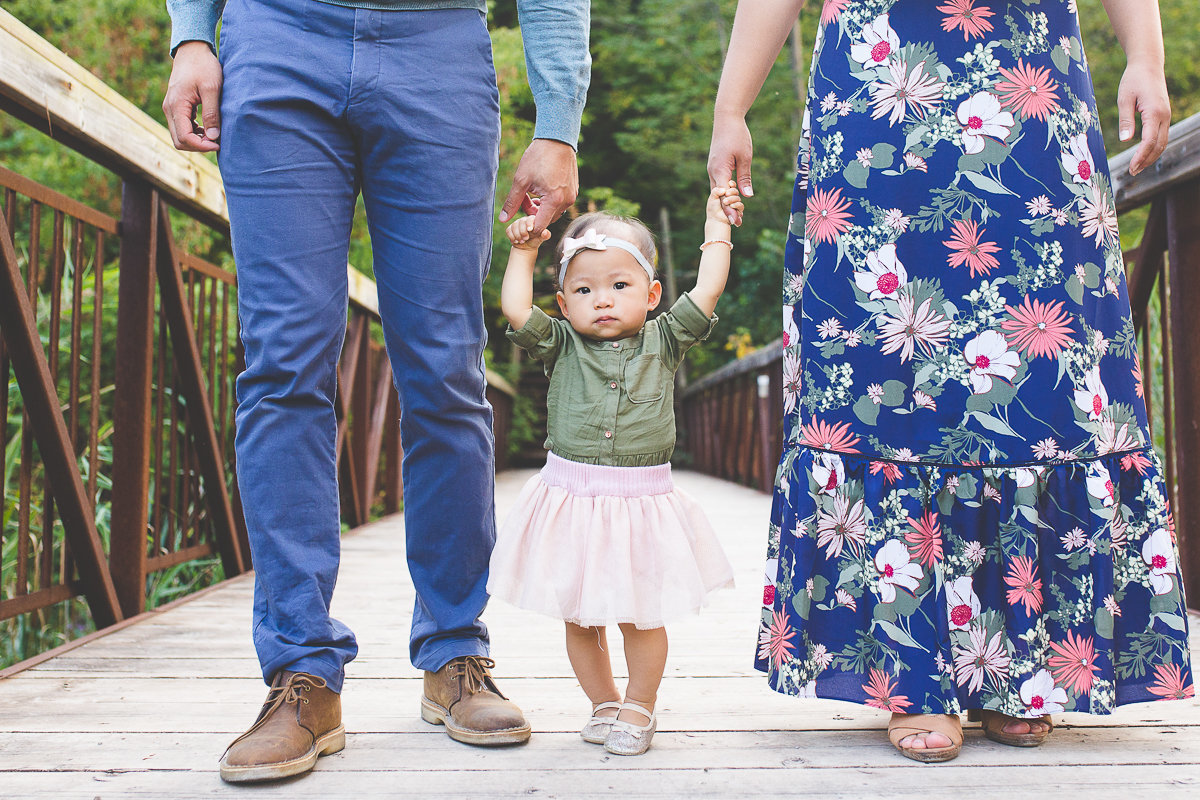 Close up of baby girl holding parent's hands {Oakville Family Photographer}