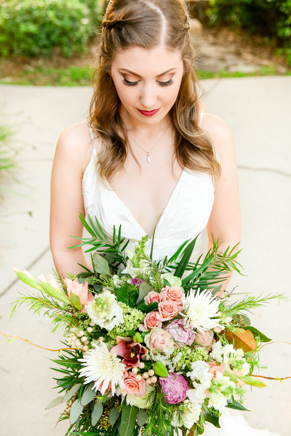 Bride with wedding day makeup in white wedding gown holds large bridal bouquet with lots of greenery and white flowers