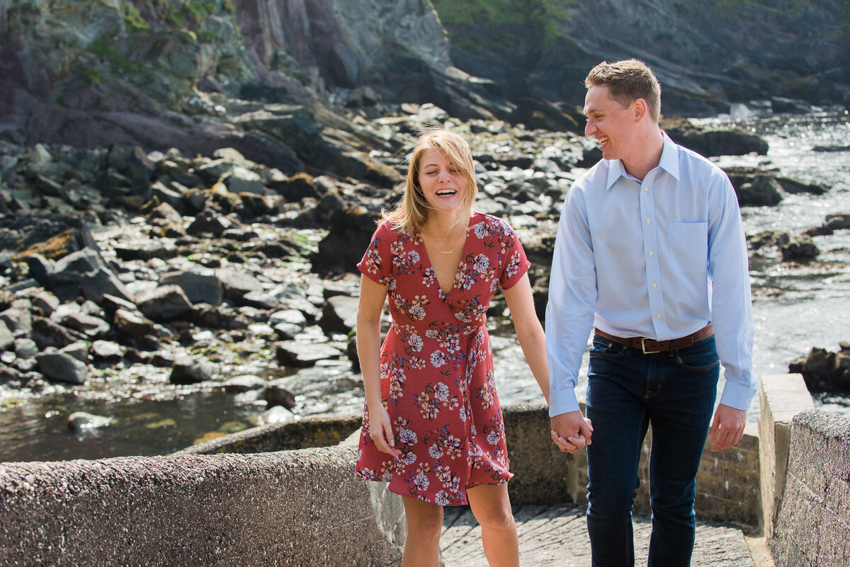 young couple walking up pier, holding hands and laughing in the sunshine