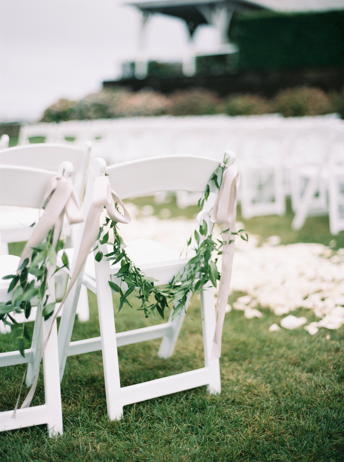Wedding ceremony chairs with greenery and ribbon for Cape Cod wedding weekend by top destination wedding planner Always Yours Events