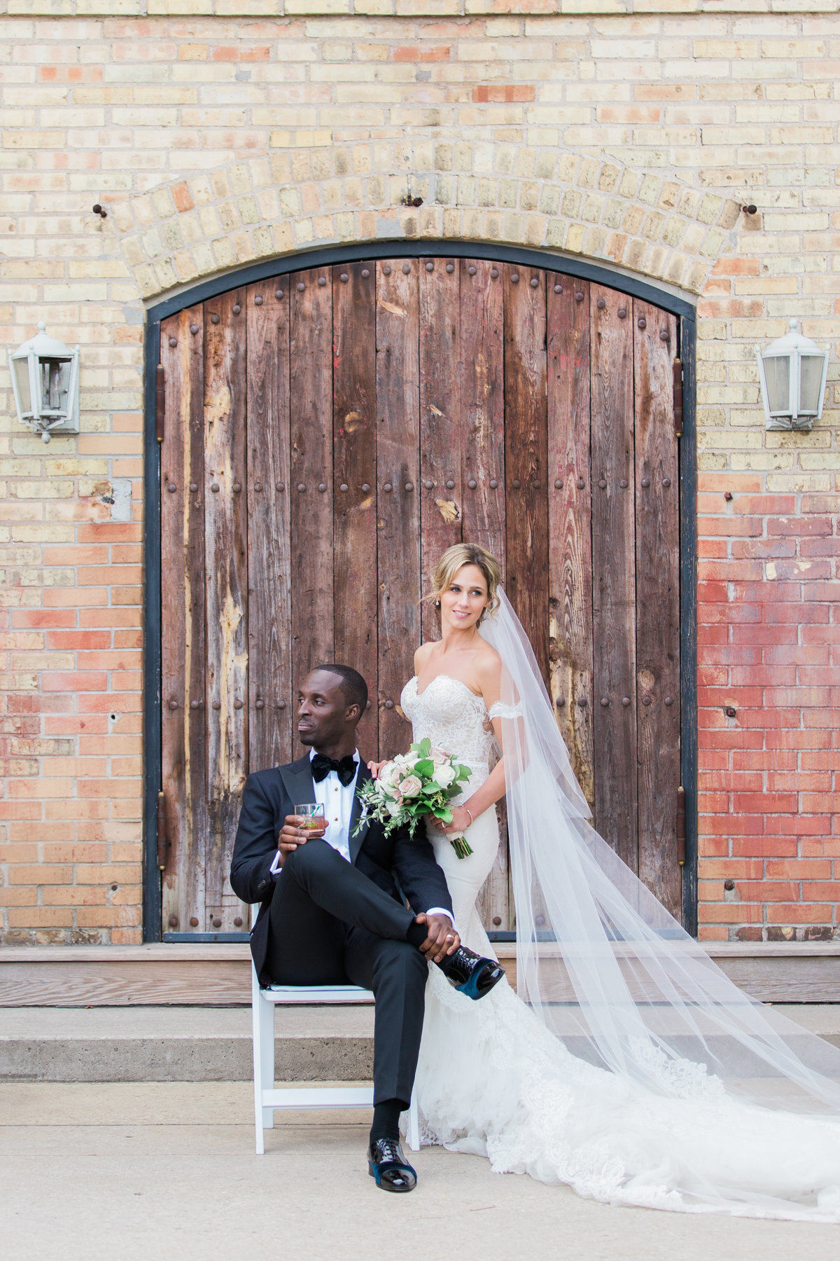 groom sitting on chair with bride in front of old door