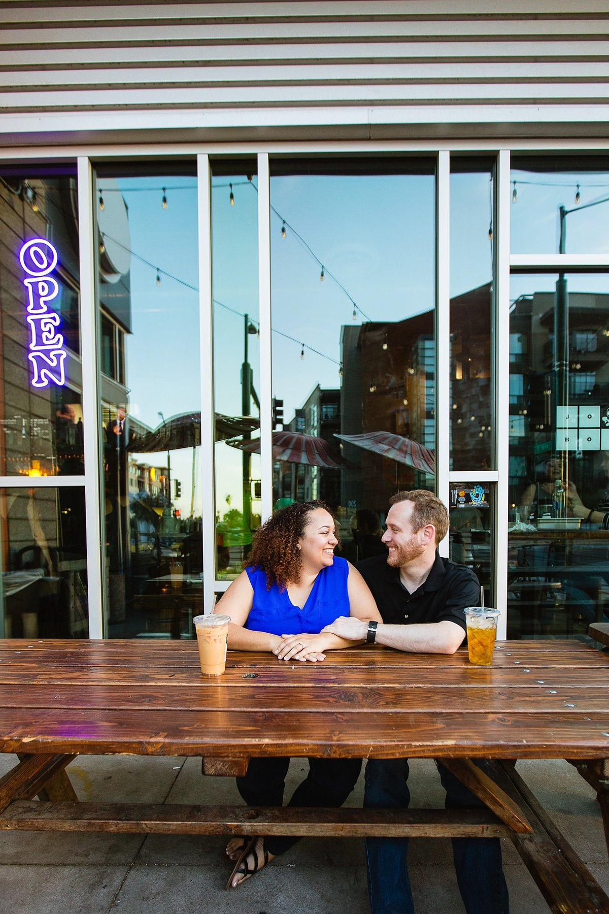 Multi-cultural couple laughing together during their coffee shop engagement session in downtown Phoenix by PMA Photography.