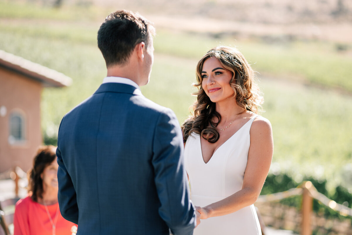 Bride and groom exchanging vows during Lake Chelan wedding ceremony at Tsillan Cellars