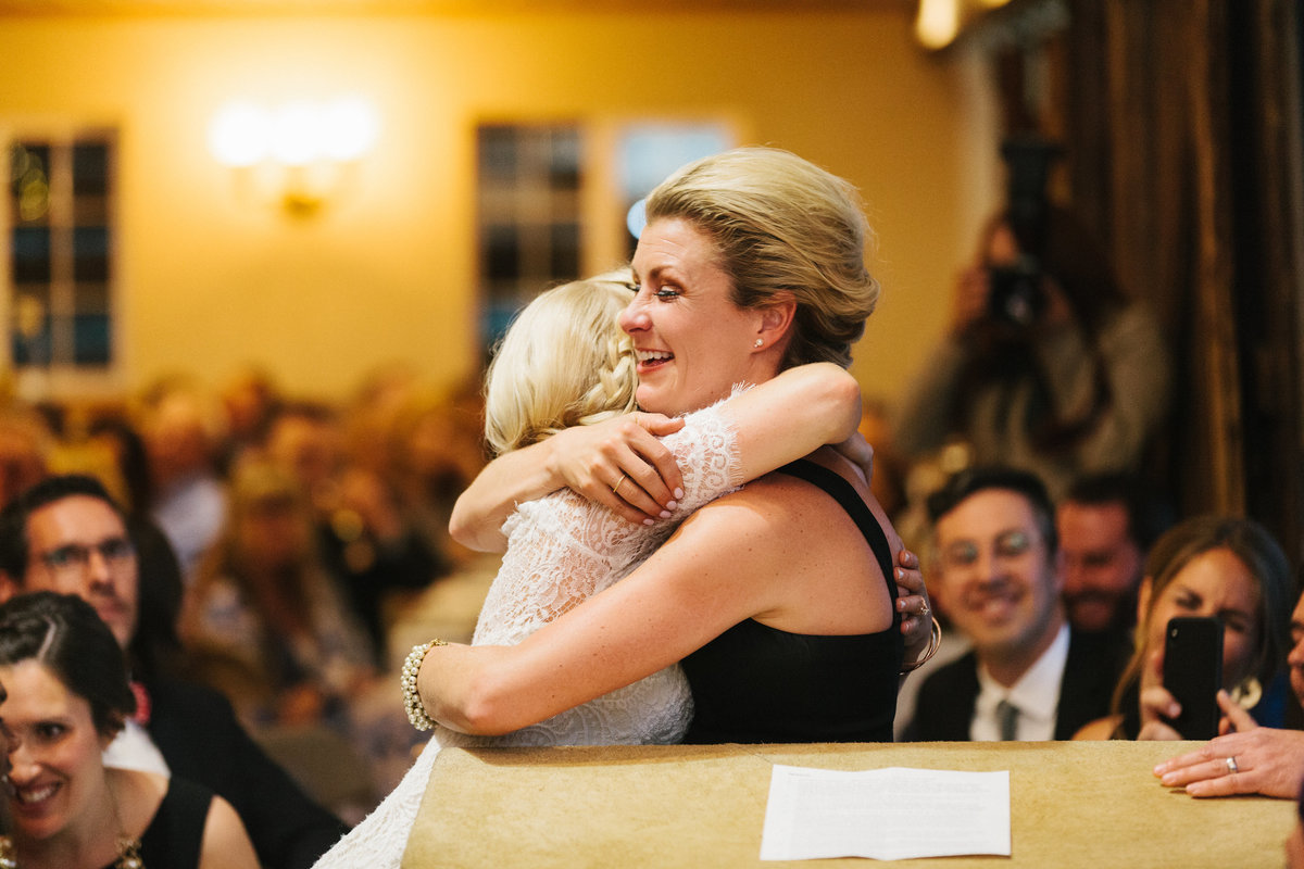 Two women friends hugging after a speech.