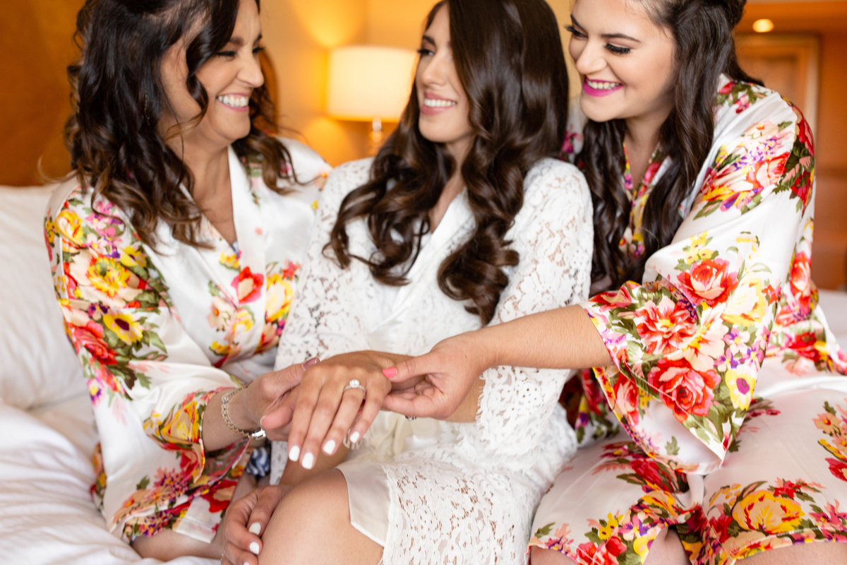 Bride shows off her round cut  engagement ring on her wedding day with her bridesmaids in their white and pink floral bridesmaid robes on their white hotel bed while they are getting ready on her wedding day
