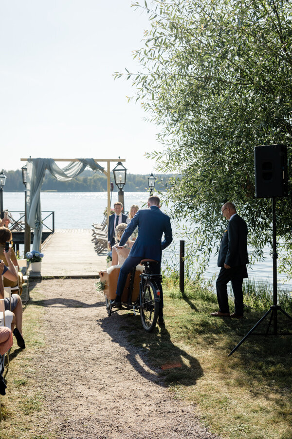 Groom driving bride on bicycle arrive at outdoor summer wedding ceremony by the water at Krusenberg Herrgård