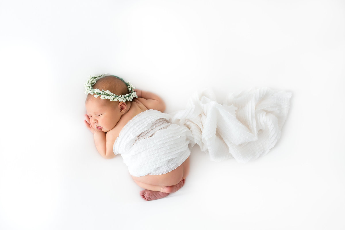 baby girl sleeping with floral crown and white fabric draped over her {Oakville Newborn Photographer}