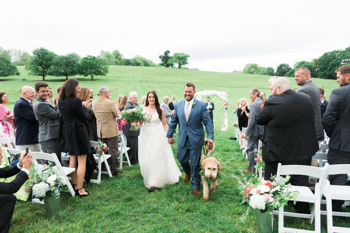 Bride and groom with dog going down aisle