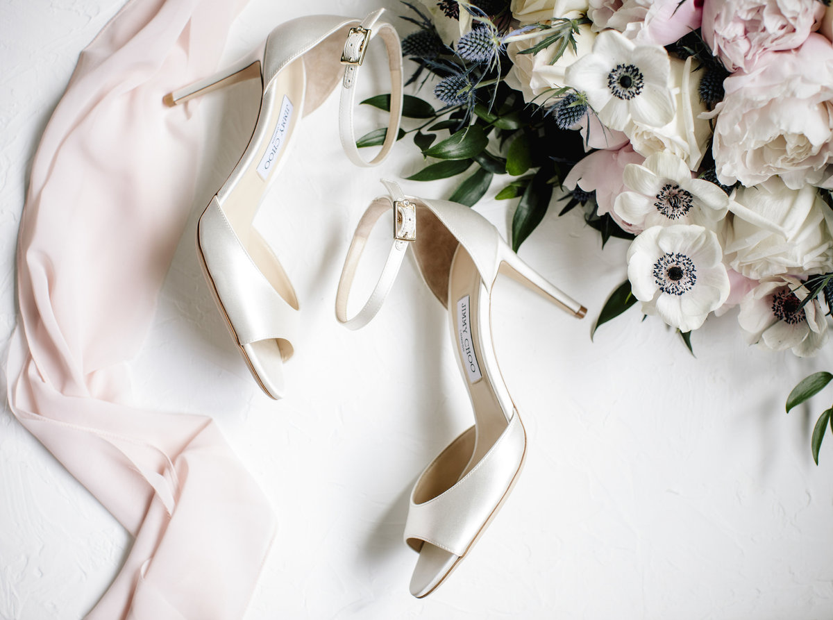 wedding shoes next to flowrs