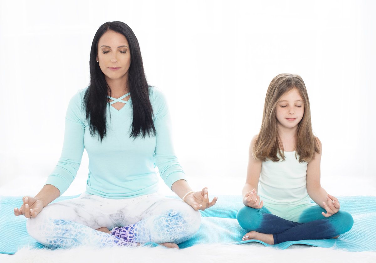 yoga instructor busniess branding photo teaching young kids  breathing and  excercises sitting on floor with eyes closed
