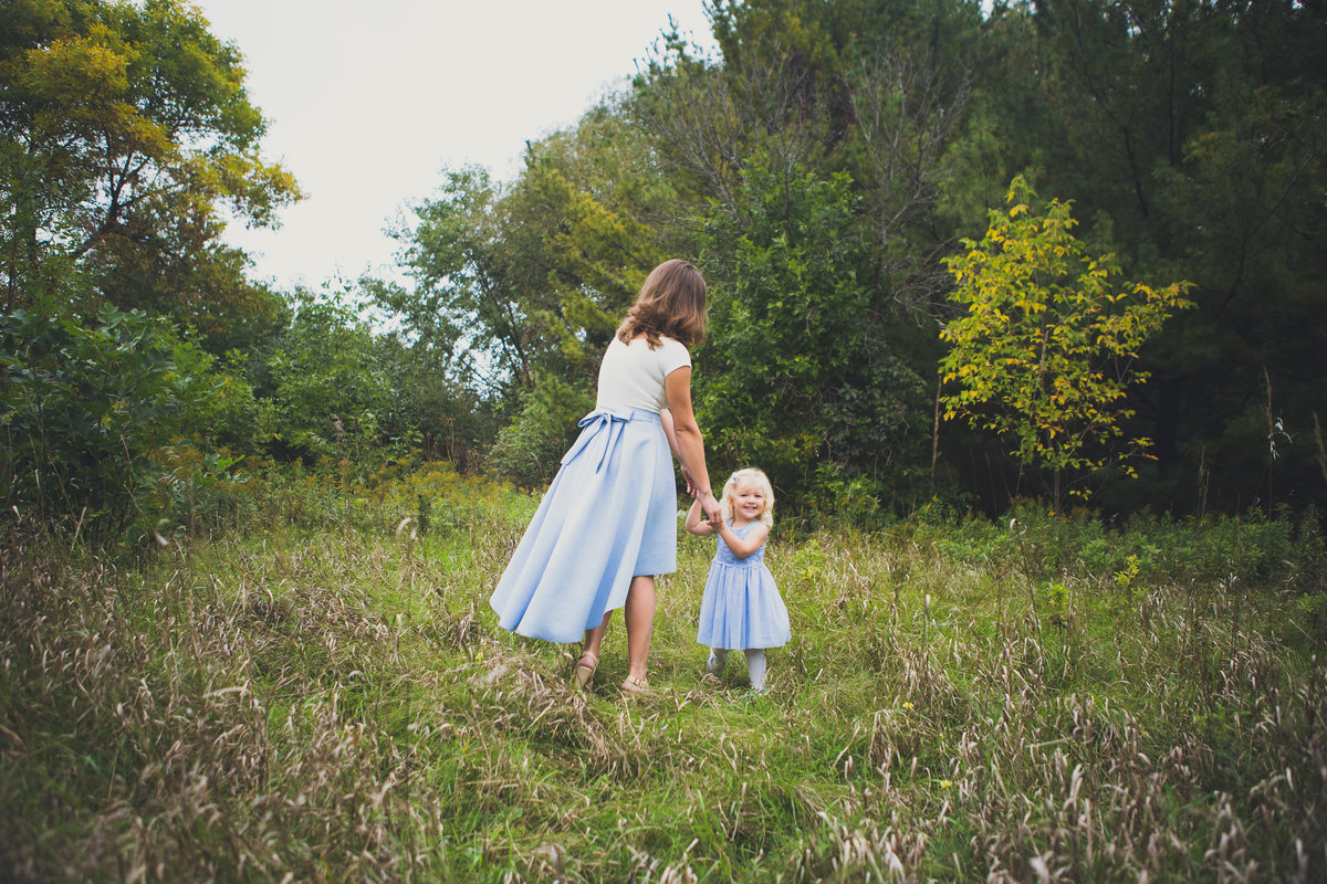 Mother and daughter spinning in field {Milton Family Photographer}