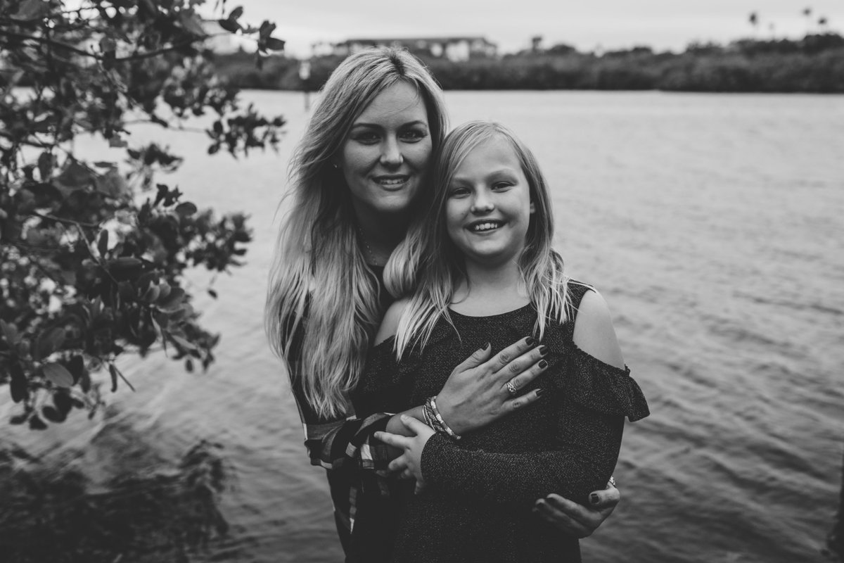 Mom and daughter embracing near water during omaha family session