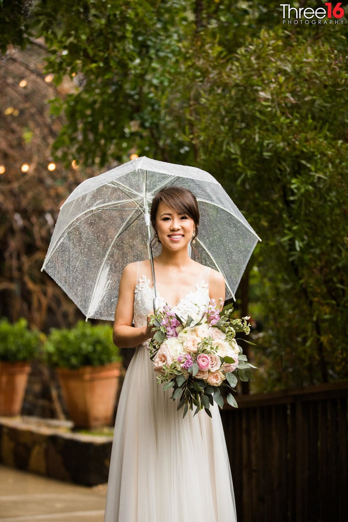 Bride posing with an umbrella and beautiful bouquet of flowers