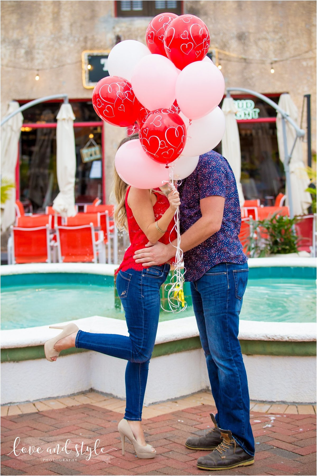 Sarasota Engagement Photography of couple kissing  behind red and pick balloons downtown