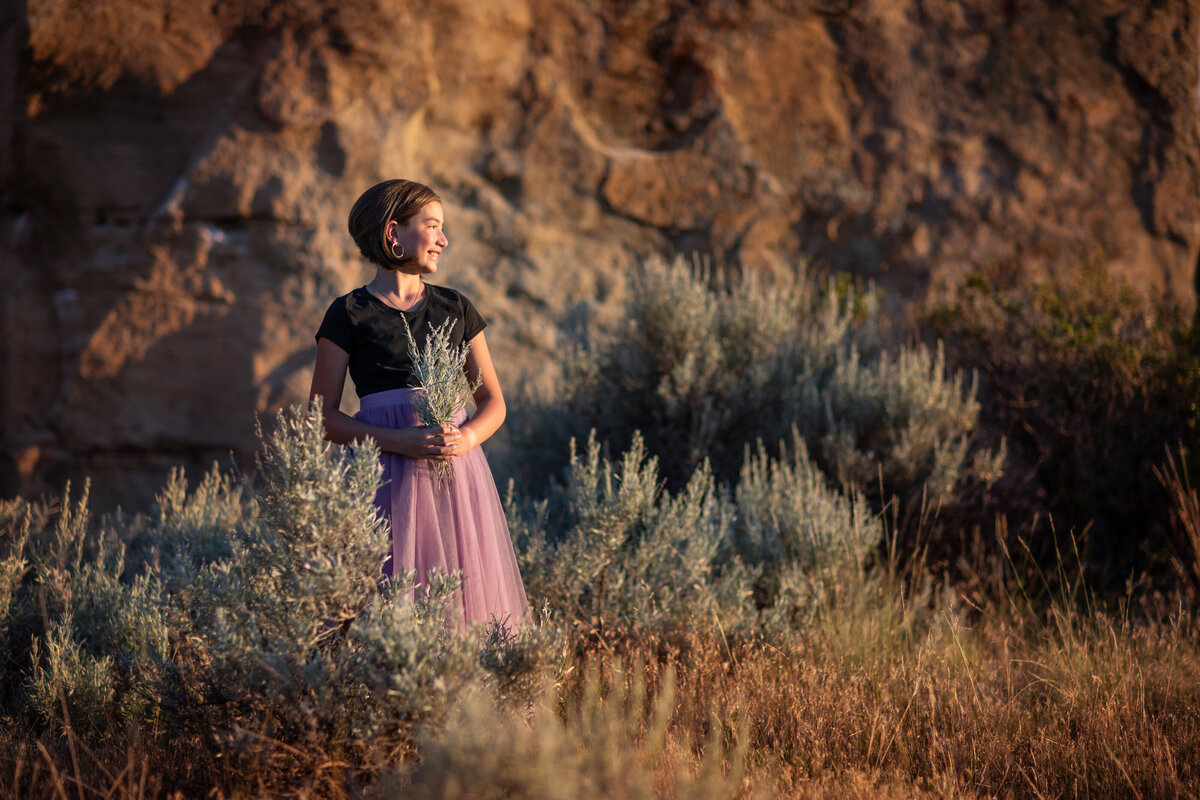 photograph of girl in purple and black dress holding sage brush, dark hair, taken at phipps park in billings mt during the summer at sunset.