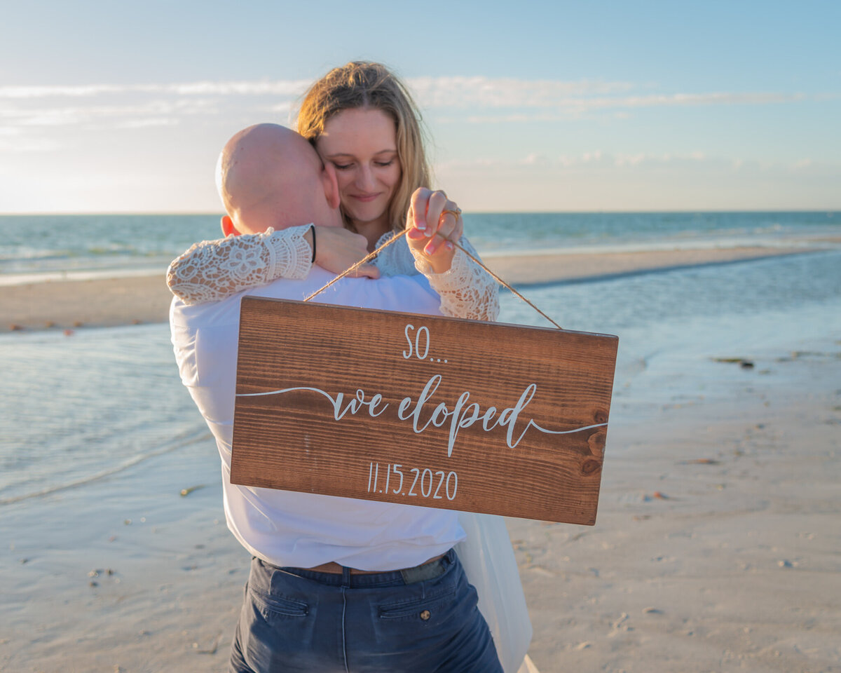 "Groom holding his bride on the beach with a sign saying ""So... We eloped"""