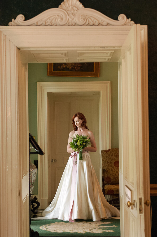 red-haired bride wearing an a-line style wedding dress with pink waistband and holding a green flower wedding bouquet while standing in the doorway of Ballyseede Castle