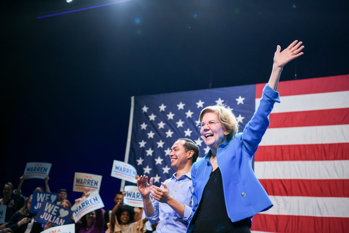Elizabeth Warren and Julian Castro waving to the crowd in front of American flag