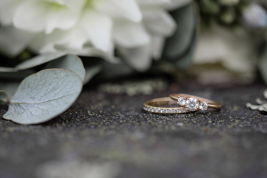 Close up of gold wedding rings with diamonds lying on the ground in front of flowers